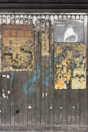 Old vintage retro japanese movie posters on underpass Yurakucho Concourse wall under the railway line of the station Yurakucho. Japanese noodle stalls and sake bars revive the nostalgic years of Showa air with old samurai posters and placards glued to the