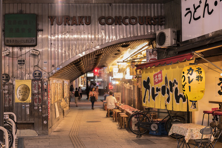 Night view of Yurakucho Concourse underpass under the railway line of the station Yurakucho. Japanese noodle stalls and sake bars revive the nostalgic years of Showa air with old posters and placards glued to the walls of the tunnel. Editorial