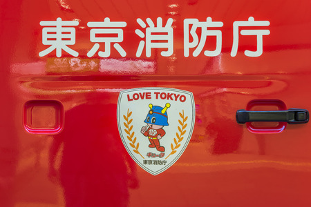 View of a red Japanese fire truck door handle with ideograms signifying Tokyo firefighters and firemen's mascot with the emergency number 119 on the chest and the LOVE TOKYO slogan on an escutcheon sticker.