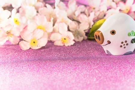 Pink glitter background with sakura cherry blossoms for japanese New Year's Cards with cute animal figurine of boar or pig. Banco de Imagens - 113833090