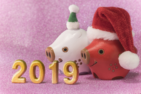 Pink glitter background for New Year's Cards with cute animals figurines of two boars or pigs with a Christmas hats and handmade golden numbers of 2019 year.