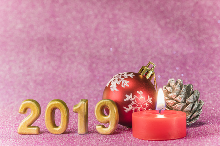 Pink glitter background for New Years Cards with Christmas tree ball and silver bread apple around a candle and handmade golden numbers of 2019 year.