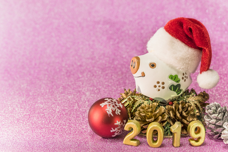 Pink glitter background for New Year's Cards with a funny boar with a Christmas hat, a X'Mas tree ball and a silver bread apple around a handmade golden numbers of 2019 year.