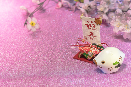 Glitter background for japanese New Years Cards with cute animal figurine of boar or pig and rice paper with handwriting ideograms Geishun which means Welcome Spring.