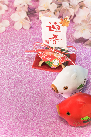 Pink glitter background with sakura cherry blossoms for japanese New Years Cards with cute animals figurines of two boars or pigs and rice paper on bamboo stand with handwriting ideograms Geishun which means Welcome Spring.
