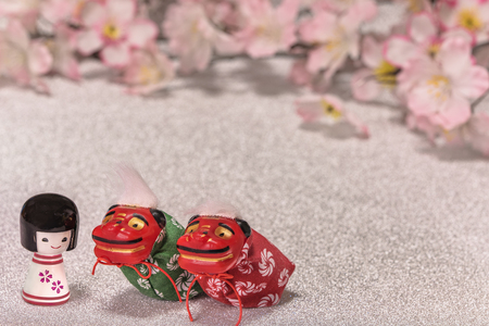 Japanese New Year's Cards with little doll Kokeshi and cute folklore animals figurines of two lions Shishimai on glitter silver background with a branch of cherry blossoms flowers.
