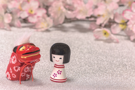 Japanese New Year's Cards with little doll Kokeshi and cute folklore animal figurine of lion Shishimai on glitter silver background with a branch of cherry blossoms flowers.
