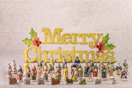 Small figurines of santons from French Provence used like beans of the cake of the kings during the Epiphany also called the Little Christmas with in back the golden word Merry Christmas.