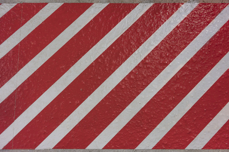 Sticker texture with red and white stripes diagonally on a concrete surface. Standard-Bild