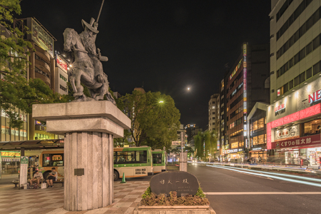 Night view of the square in the Nippori train station in the Arakawa district of Tokyo with a statue of a horse by Ota Dokan who was a 15th century Japanese samurai warrior-poet, military tactician and Buddhist monk. D? kan is best known as the architect