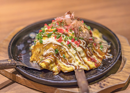 Japanese okonomiyaki covered with katsuobushi leek mayonnaise and bulldog sauce served on a hot plate with spatulas.