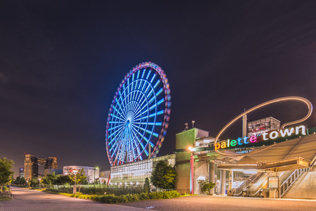 TOKYO, JAPAN - AUGUST 24 2018: Odaiba illuminated Palette Town Ferris wheel named Daikanransha visible from the central area of Tokyo in the summer night sky. Passengers can see the Tokyo Tower, Rainbow Bridge twin-deck, and Haneda Airport, Tokyo during t