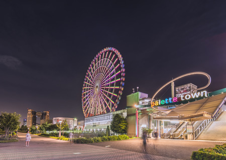 TOKYO, JAPAN - AUGUST 24 2018: Odaiba illuminated Palette Town Ferris wheel named Daikanransha visible from the central area of Tokyo in the summer night sky. Passengers can see the Tokyo Tower, Rainbow Bridge twin-deck, and Haneda Airport, Tokyo during t Sajtókép