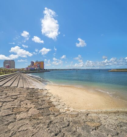 Beach coast lined with palm trees of Distortion Seaside, Oak fashion, Depot Island Seaside buildings and Vessel Hotel Campana in the vicinity of the American Village in Chatan City of Okinawa. Stok Fotoğraf - 128012283