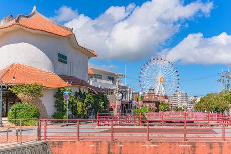 Chatan, Japan - September 17, 2018: Chatan City Red Steel Bridge and Mihama Carnival Park Ferris wheel in the American Village Editöryel