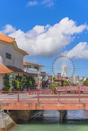 Chatan, Japan - September 17, 2018: Chatan City Red Steel Bridge and Mihama Carnival Park Ferris wheel in the American Village Stok Fotoğraf - 127812957