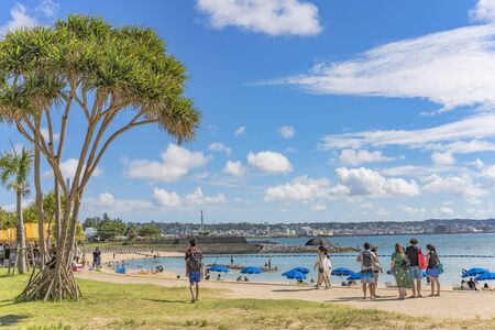 Chatan, Japan - September 17, 2018: Beach umbrellas and palm trees on the beach in Chatan City in the American Village of Okinawa island in Japan.