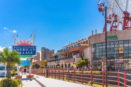 American Village, Japan - September 17, 2018: Chatan City Red Steel Bridge and Mihama Carnival Park Ferris wheel in the American Village