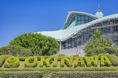 GINOWAN, JAPAN - September 16 2018: Building of Okinawa Convention Center decorated with palm trees near the tropical beach of Ginowan City