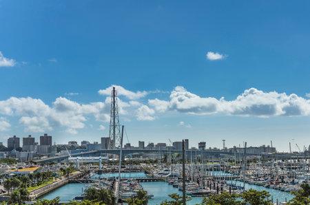GINOWAN, JAPAN - September 16 2018: Leisure boats in the Ginowan harbor marina seen from Okinawa conversion center Stok Fotoğraf - 127548547