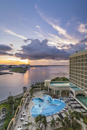 Naha, Japan - September 17, 2018: Sunset over the butterfly-shaped swimming pool of Leisure Hotel and the sea of Sumiyoshi district of Naha City in Okinawa island.