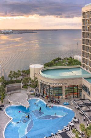 Naha, Japan - September 17, 2018: Sunset over the butterfly-shaped swimming pool of Leisure Hotel and the sea of Sumiyoshi district of Naha City in Okinawa island. Stok Fotoğraf - 127813004