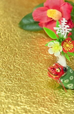A Japanese greeting card with a Tsubaki flower also called the winter rose and an adorable Japanese Folklore animal figurine depicting a Shishimai lion with an ornq,ent decorated with the Japanese Kotobuki ideogram which means longevity on a golden crumpled paper.