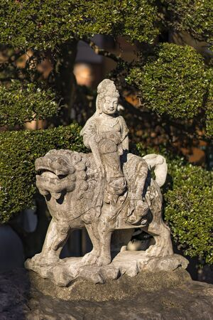 Tabata, Japan - January 03 2019: Stone statue of Togakuji temple in Tokyo depicting Japanese bodhisattva Monju Bosatsu on his blue tiger symbolizing wisdom and intelligence in Buddhism.