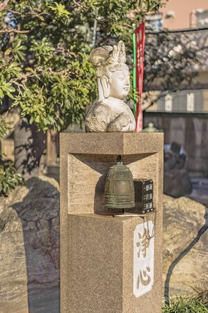 Tabata, Japan - January 03 2019: Small marble statue depicting the head of the buddhist goddess of compassion Kannon Bosatsu with its base the word which is for gratitude, Kuy for memorial service and Kigan for prayer. Stockfoto - 133186254