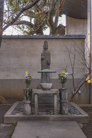 Tokyo, Japan - January 03, 2019: Stone statue depicting the Buddha Yakushi Nyorai with two vases filled with chrysanthemums in the Tokyo Tennoji.