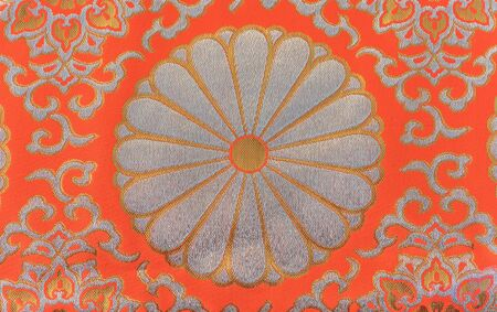Texture of a silver and orange embroidered textile of chrysanthemum flowers symbol of the Emperor of Japan. Foto de archivo