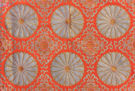 Texture of a silver and orange embroidered textile of chrysanthemum flowers symbol of the Emperor of Japan.
