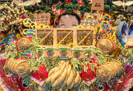 tokyo, japan - march 18 2020: Abundance of decorations in the effigy of deities and lucky charms of Japanese folklore like Ebisu god of fishing, Daikokuten god of harvests, Otafuku goddess of mirth on a giant Engi Kumade which means Auspicious Rake sold e