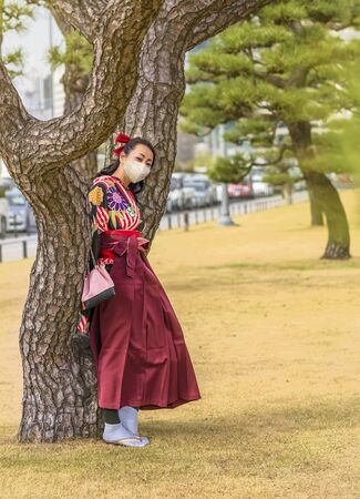 Japanese woman dressed in a hakama kimono and wearing a facial mask leaned  against the trunk of a pine tree