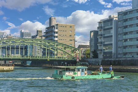 Cleaning boat in front of Mannenbashi iron bridge removing marine plastics debris drifting in Sumida river to avoid them to go out into the sea of Tokyo.