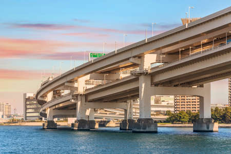 Double-layered suspension Rainbow Bridge on the Tokyo Bay against a sunset sky with the shuto expressway Daiba route on upper and the yurikamome monorail below.