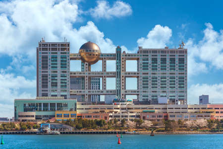tokyo, japan - april 04 2020: Seascape of Aqua City shopping centers on the island of Odaiba with the building of the Japanese television channel Fuji TV famous for its Hachitama observation area in spring.