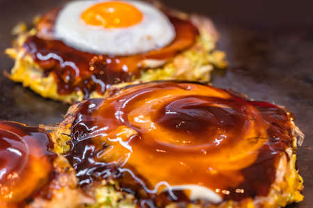 Close-up on a fried egg and an okonomiyaki Japanese omelet prepared with shredded cabbage, cooked on both sides on a hot plate and brushed over in circle with oyster and worcestershire sauce.