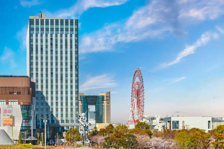 Tokyo, Japan - March 01 2020: Life-Sized Unicorn Gundam Statue in front of the buildings of DiverCity Tokyo Plaza with the soaring ferris wheel Daikanransha and the Baycourt Club Hotel in the back.