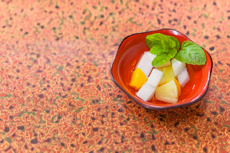 Japanese traditional dessert of Annin tofu or almond tofu made of apricot kernel milk, agar, and sugar with fruits pieces like pineapples and apricot and a mint leaf.