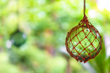 Close-up on japanese traditional handmade glass fishing floats Bindama or Ukidama in a nets hanging against a bokeh background.