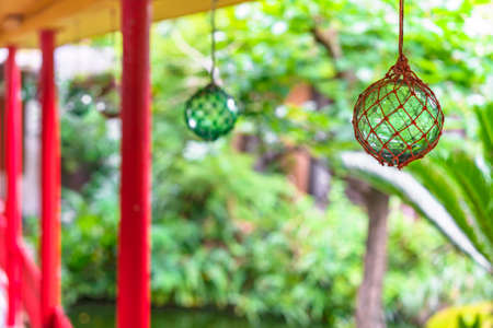 Japanese traditional handmade glass fishing floats Bindama or Ukidama in a nets hanging against a bokeh background.
