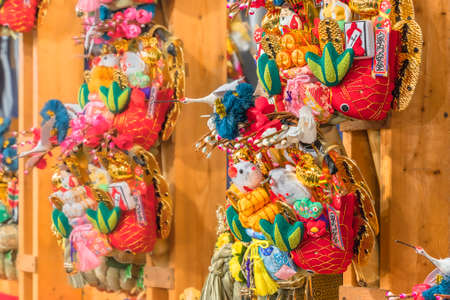 Close-up on auspicious rakes or kisshō kumade made in chirimen crêpe fabric decorated with mouses, sea breams and cranes in the Tori-no-Ichi Fair of Ootori shrine.