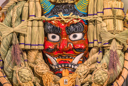 Giant auspicious rake made of straw and papier-mâché decorated with a scary demon face of the Japanese folklore Namahage, turtles and a rooster at Tori-no-Ichi Fair.