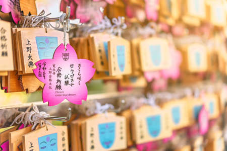 tokyo, japan - october 10 2020: Pink cherry blossom shaped Ema plaques famous among students during exams because like the face of Ueno Giant Buddha fallen down in earthquake they can't fail anymore. Editorial