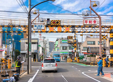 tokyo, japan - october 11 2020: Cars traffic passing over a level crossing in the local shopping district of Kanegafuchi street adjacent to the Kanegafuchi station in the Sumida ward of Tokyo. 新聞圖片