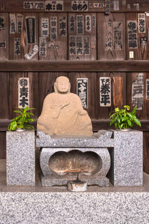tokyo, japan - november 01 2020: Buddhist sculpture of the monk Kūkai known as K�b�-Daishi founder of the Japanese Shingon sect against a wall of Tamonji temple full of votive slips named senjafuda.