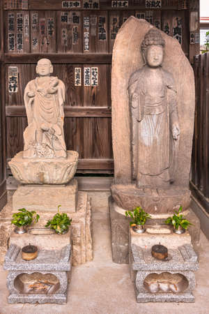 tokyo, japan - october 30 2020: Buddhist sculptures of the bodhisattva Kosodate Jizo statue protecting children and the Buddha Shaka Nyorai lined up from left to right in the Tamonji temple of Sumida