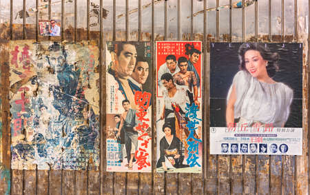 tokyo, japan - january 26 2021: Torn old vintage japanese posters of samurai or yakuza retro movies and pop music idol stuck on the rusted wall of Yuraku Concourse underpass at Yurakucho station.
