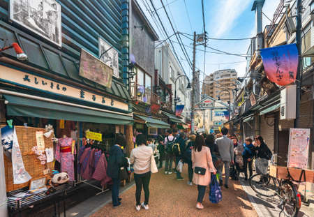 tokyo, japan - april 05 2019: Old-fashioned Yanaka-Ginza shopping street with pedestrians enjoying strolling and shopping through the traditional retro stores of Japanese kimono and yukata.